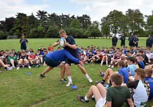 Coaches Ben Armstrong and Will Matthews demonstrate tackle technique to participants during a Leinster School of Excellence Camp