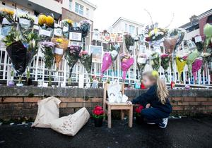 A young girl looks at tributes to the victim near                   the scene where Lorcan O'Reilly was killed