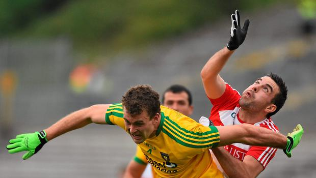 Derry's Caolan O'Boyle battles with Donegal's Eamonn McGee for control of the ball