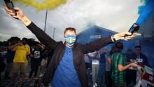 Leeds United fans celebrate outside Elland Road after Huddersfield Town beat West Bromwich Albion to seal their promotion to the Premier League. Photo credit: Nick Potts/PA Wire.