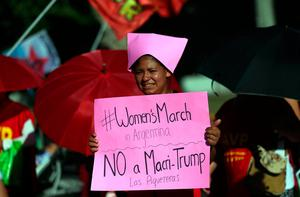 "A woman wear a pink protest hat, symbol of the anti-Trump women's march, during a protest outside the U.S. embassy in Buenos Aires, Argentina, January 20, 2017. The signs read ""No to Trump - Leftist socialist (party)"" REUTERS/Marcos Brindicci"