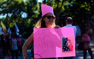 "A woman wearing a pink protest hat, symbol of the anti-Trump women's march, holds a sign that reads ""Black Muslim lives matter"" during an anti U.S. President Donald Trump protest outside the U.S. embassy in Buenos Aires, Argentina, January 20, 2017. "" REUTERS/Marcos Brindicci"