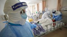 Protection: Medical workers in masks and protective clothing tend to a coronavirus patient in Wuhan. Picture: Reuters