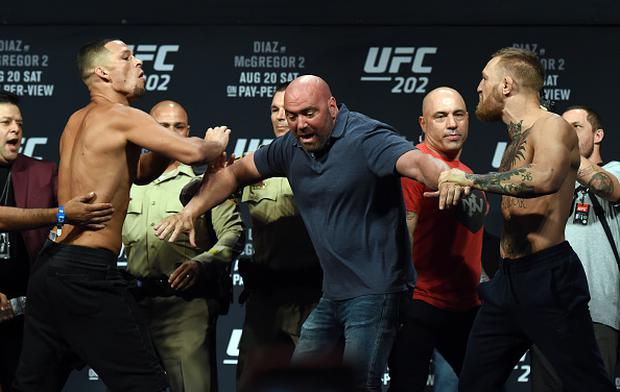 UFC President Dana White (C) separates Nate Diaz (L) and UFC featherweight champion Conor McGregor as they face off