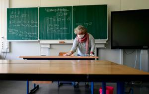 A teacher cleans and disinfects chairs and tables at the the Phoenix Gymnasium secondary school in Dortmund, Germany, amid the novel coronavirus COVID-19 pandemic. Photo: AFP via Getty Images