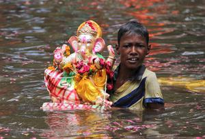 A boy carries an idol of the Hindu elephant god Ganesh, the deity of prosperity, after it was immersed in a pond during the ten-day-long Ganesh Chaturthi festival at Ajmer in the desert Indian state of Rajasthan September 7, 2014.