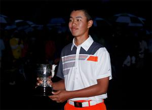 Guan Tianlang of China holds the trophy he was awarded for low amateur