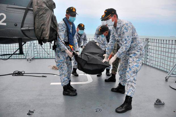 In this photo released by the Royal Malaysian Navy, navy sailors carry an unidentified body on to the deck of KD Lekiu frigate after it was recovered in the waters off the Johor coast of Malaysia, Tuesday, Aug. 22, 2017. The commander of the U.S. Pacific Fleet said some remains of Navy sailors were found in a compartment of the USS John McCain on Tuesday, a day after the warship's collision with an oil tanker in Southeast Asian waters left 10 sailors missing. (Royal Malaysian Navy via AP)