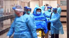 Worry: Medical staff transfer a patient with a suspected case of coronavirus at the Queen Elizabeth Hospital in Hong Kong. Photo: Reuters