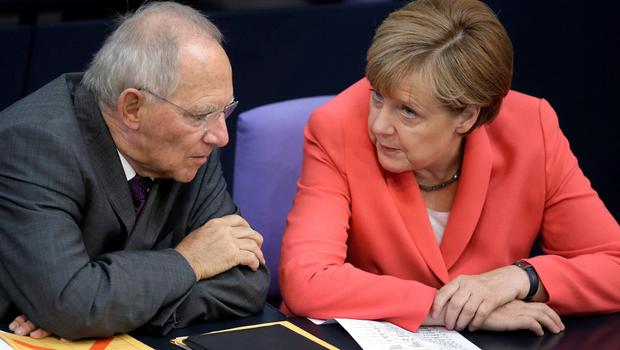 German Finance Minister Wolfgang Schaeuble, left, and Chancellor Angela Merkel, right, speak during a meeting of the German federal parliament, Bundestag, in Berlin, Germany, Thursday, June 18, 2015. (AP Photo/Michael Sohn)
