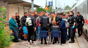Police officers stop refugees after taking them off the train at the rail station in Freilassing, Germany (AP Photo/Kerstin Joensson)