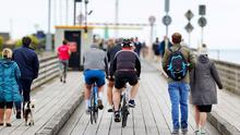 Very little sign of social distancing as cyclists, joggers, children, adults and dog walkers pass each other on the wooden bridge at Dollymount. Photo: Steve Humphreys