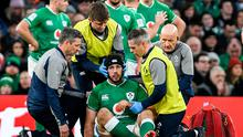 Caelan Doris of Ireland is treated for an injury resulting in him having to leave the game