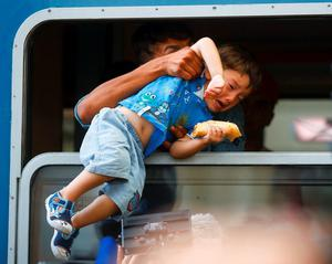 A migrant pulls a boy inside a train through a window at the Keleti train station in Budapest, Hungary, September 3, 2015.        REUTERS/Leonhard Foeger   TPX IMAGES OF THE DAY