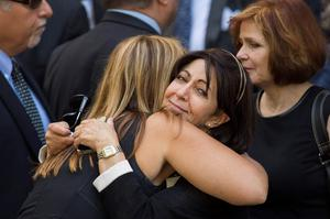 Mourners embrace while departing the funeral of comedian Joan Rivers at Temple Emanu-El in New York September 7, 2014. REUTERS/Lucas Jackson