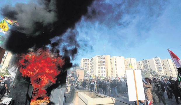 Iraqi protesters set a sentry box ablaze in front of the US embassy in Baghdad amid fury over US air strikes. Photo: Getty Images