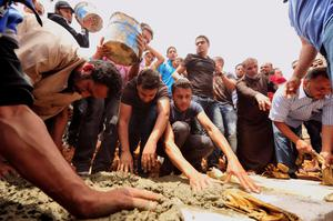 People attend a funeral ceremony of one of those killed in the car bombing yesterday near the Galaa Hospital in Benghazi
