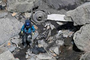 A French rescue worker inspects the debris from the Germanwings Airbus A320 at the site of the crash, near Seyne-les-Alpes, French Alps March 29, 2015.  REUTERS/Gonzalo Fuentes