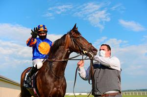 Sign of peace: A triumphant Seamie Heffernan aboard Aidan O'Brien-trained Peaceful with groom Leigh O'Brien after winning the Tattersalls 1,000 Guineas. Photo: PA Wire