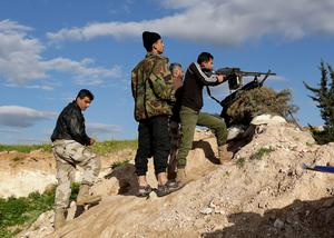 A rebel fighter aims his weapon at Morek front line in the northern countryside of Hama, in Syria
