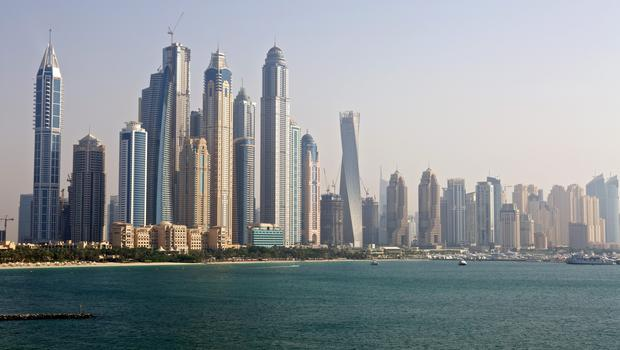 City skyscrapers stand on the waterfront seen from a construction site of residential apartments on Palm Jumeirah artificial island in Dubai