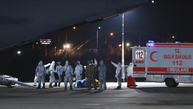 Medical personnel work around a military plane at the airport in Ankara, Turkey, shortly after it landed after flying from Wuhan, China (Huseyin Avci/Turkish Ministry of Health via AP)