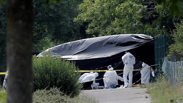 Police officers investigate at a plant where an   attack took place, Friday, June 26, 2015 in Saint-Quentin-Fallavier, southeast of Lyon, France.  A man with suspected ties to French Islamic radicals rammed a car Friday into an American gas factory in southeastern France, triggering an explosion that injured two people, officials said. The severed head of a local businessman was left hanging at the factory's entrance, along with banners with Arabic inscriptions, they said.  (AP Photo/Laurent Cipriani)