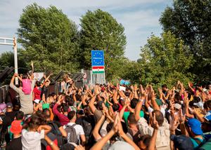 Migrants shout slogans at the closed railway border crossing between Serbia and Hungary