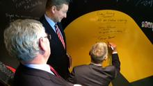 Taoiseach Enda Kenny and Tanaiste Eamon Gilmore watch Minister for Jobs and Enterprise Richard Bruton sign a wall at Wayra in Dublin
