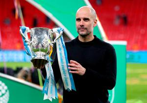 Manchester City manager Pep Guardiola holds the Carabao Cup trophy. Photo: Mike Egerton/PA Wire