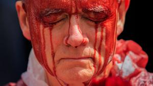Red alert: Stephen Cunningham, from Rathgar, a member of Extinction Rebellion Ireland, taking part in a Blood on our Children demonstration outside Leinster House earlier this month, which the campaign group says symbolises the inaction of the Government on climate change