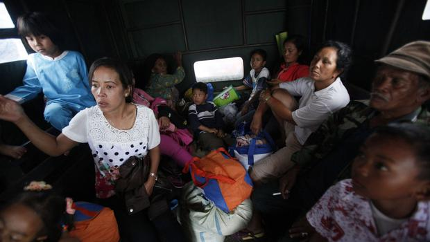 Villagers sit in a truck as they evacuate their homes on the slope of Mount Sinabung in Karo, North Sumatra, Indonesia, Wednesday, June 3, 2015. (AP Photo/Binsar Bakkara)