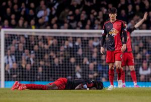 Swansea's Bafetimbi Gomis lies on the floor after collapsing at White Hart Lane