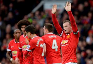 Manchester United's English striker Wayne Rooney (R) celebrates after scoring their third goal during the English Premier League football match between Manchester United and Tottenham Hotspur at Old Trafford