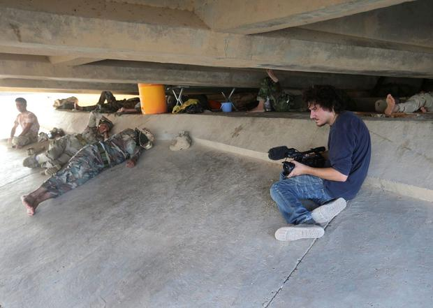 Associated Press video journalist Simone Camilli films Kurdish Peshmerga fighters under a bridge near the front line with militants of the Islamic State, in Mariam Bek village, between the northern Iraqi cities of Tikrit and Kirkuk July 1, 2014. REUTERS/Hussein Malla/AP Photo/Handout via Reuters