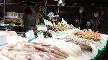 People wear protective face masks as they buy fish at La Boqueria market, amidst concerns over coronavirus outbreak, in Barcelona, Spain. REUTERS/Nacho Doce