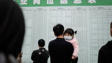 Job applicant hold a child while reading recruitment information in Wuhan, Hubei Province,China. .(Photo by Getty Images)