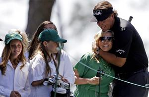 Phil Mickelson kisses his wife Amy as his daughters look on after teeing off on the first hole during the par three competition. Photo: Reuters