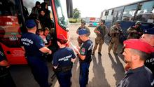 Hungarian soldiers and police stand guard as migrants get into a bus in Beremend near the Hungarian-Croatian border on September 18, 2015.  More than 20 busloads of migrants arrived at Croatia's northeastern frontier with Hungary where more than 250 Hungarian police and soldiers were deployed, an AFP correspondent said. AFP PHOTO / LASZLO LAUFERLASZLO LAUFER/AFP/Getty Images