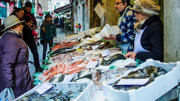 Sellers and shoppers in the Rialto market, in Venice,