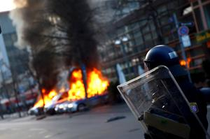 A policeman looks on as German police cars, set on fire by anti-capitalist protesters, burn near the European Central Bank (ECB) building before the official opening of its new headquarters in Frankfurt