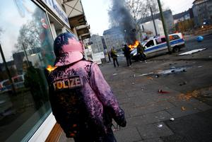 A German police officer who was hit by a paint bomb by anti-capitalist protesters looks at a burning police car near the European Central Bank (ECB) building hours before the official opening of its new headquarters in Frankfurt