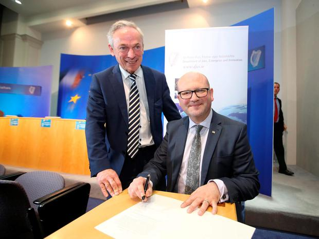 Jobs Minister Richard Bruton and Employment Minister Ged Nash sign the Minimum Wage into law yesterday. Photo Sam Boal