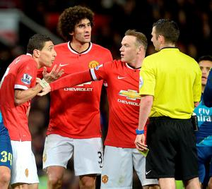 Manchester United's Angel Di Maria (left) is held by teammate Wayne Rooney as he protests to referee Michael Oliver before being sent off during the FA Cup, Sixth Round match at Old Trafford