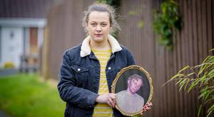 Becca Smith with a picture of innocent victim John McConville