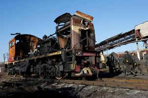 "Miners walk past a destroyed train at coal mine number 22 ""Kommunar"" in the village of Nizhnyaya Krynka, east from Donetsk, November 6, 2014"