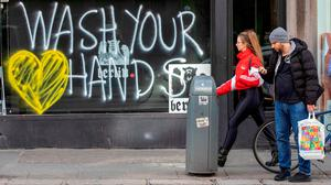 Pedestrians walk past graffiti urging people to 'wash their hands' in the Grafton Street area of Dublin. Photo: AFP via Getty Images