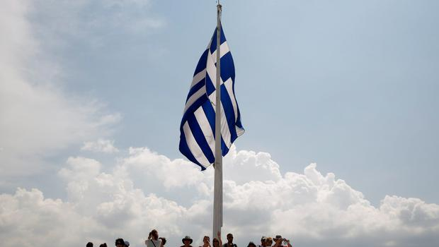 A Greek flag flutters near the Parthenon temple atop the Acropolis hill in Athens June 18, 2015. Hopes of a breakthrough at Thursday's gathering of European finance ministers, once seen as the last opportunity for an agreement, looked increasingly remote. REUTERS/Paul Hanna