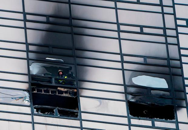 A firefighter looks out from the window of a damaged apartment in Trump Tower in New York on Saturday, April 7, 2018. The Fire Department says the blaze broke out on the 50th floor shortly before 6 p.m. Saturday. (AP Photo/Craig Ruttle)