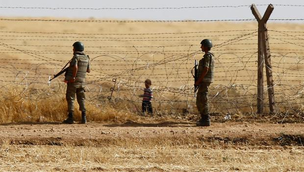 Turkish soldiers stand guard as a Syrian refugee boy waits behind the border fences to cross into Turkey on the Turkish-Syrian border, near the southeastern town of Akcakale in Sanliurfa province, Turkey, June 5, 2015. REUTERS/Osman Orsal